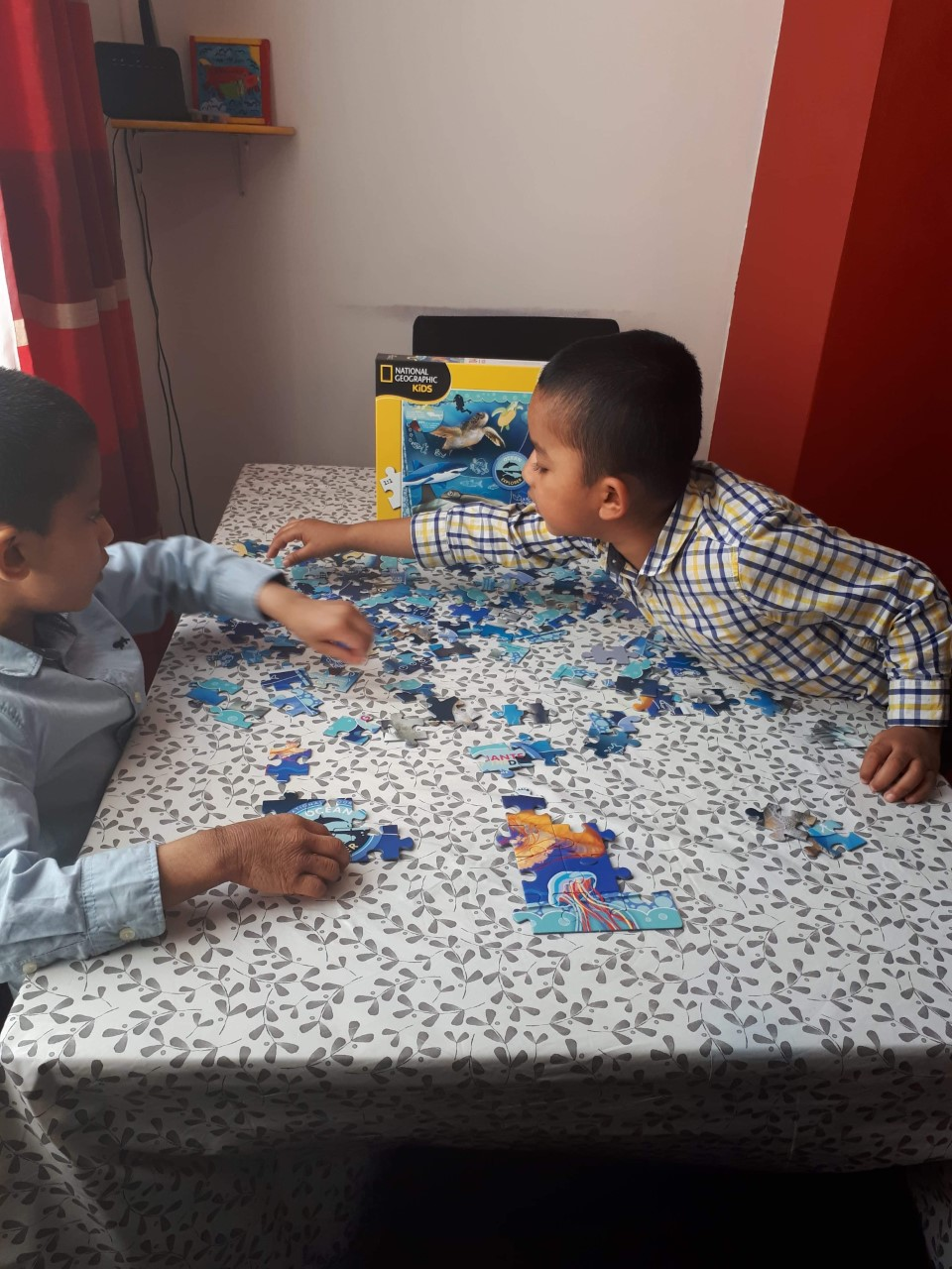 Two children work on a jigsaw together