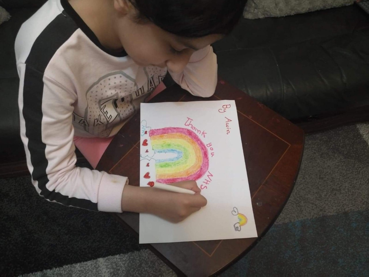A girl is drawing a picture of a rainbow, celebrating the NHS