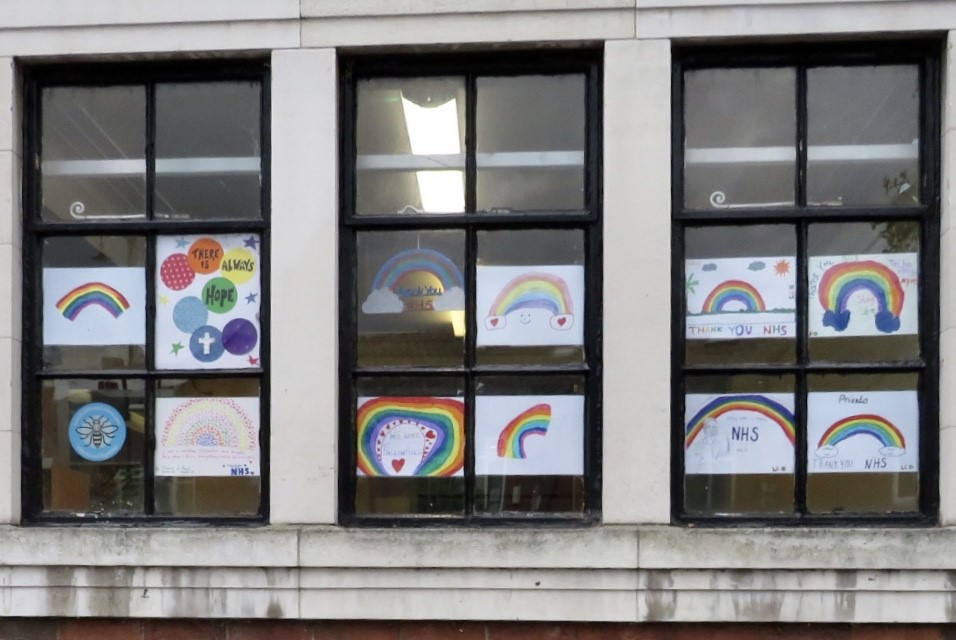Three large windows showcase multiple drawings of rainbows, celebrating the NHS