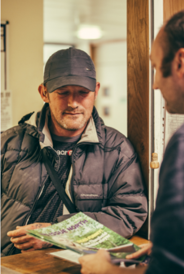 Image of Big Issue North vendor Andrew collecting a magazine.