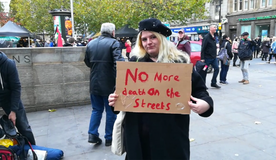 Homeless protester sign no more deaths on our streets