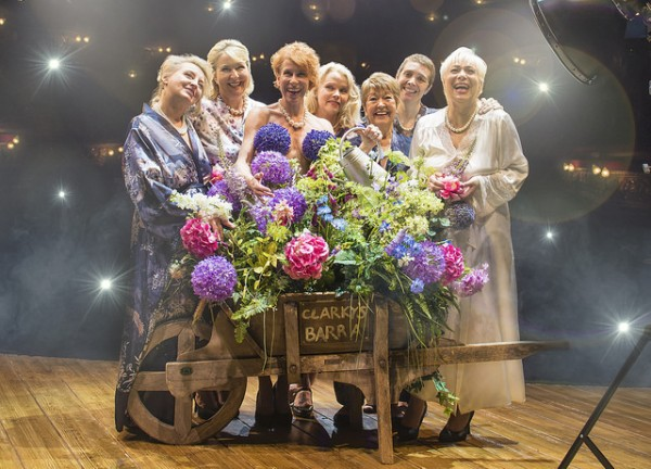 Cast of the Calendar Girls pose naked behind a wheelbarrow full of flowers