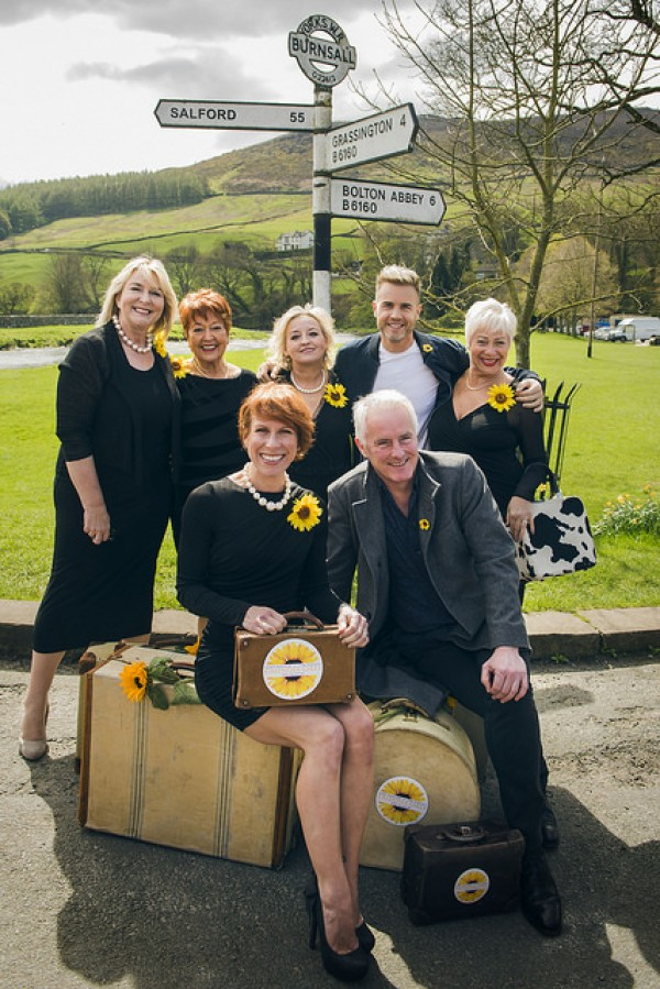 Cast of Calendar Girls with writers Gary Barlow and Tim Firth pose in front of a sign for Burnsall in Yorkshire at the start of the UK tour