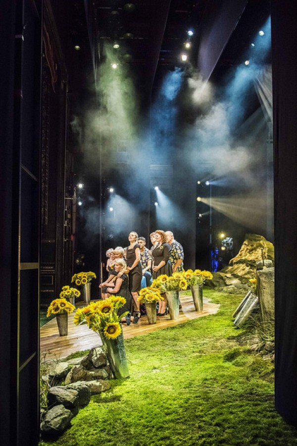 The cast on stage for the finale, surrounded by bunches of sunflowers