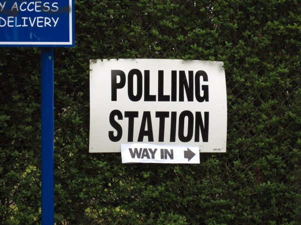 Image of a white sign that says polling station in black letters.