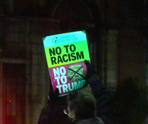 Protester holding sign down Stretford Road outside Hulme Park