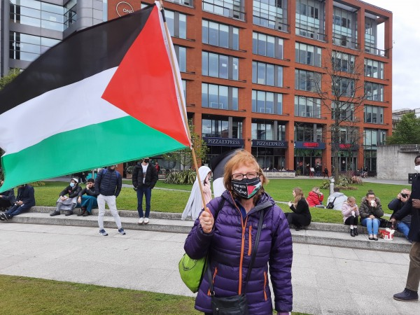 Protester Annie Hirsch waving the Palestinian flag. Photo By Victoria Thiele
