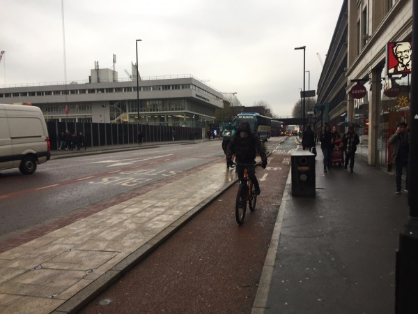 A cyclist riding down a wet Oxford Road