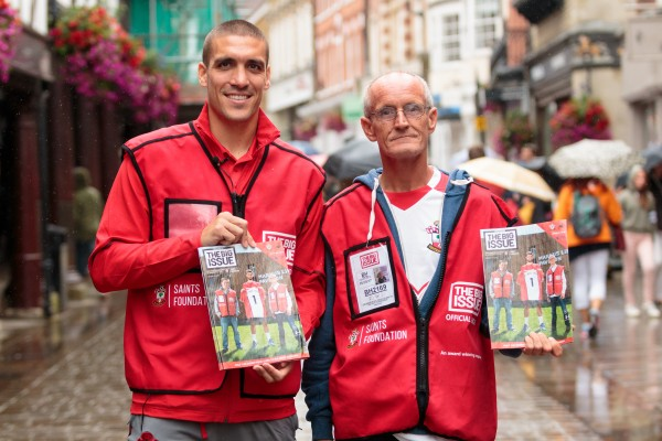 Image of two Big Issue North vendors holding magazines to sell.