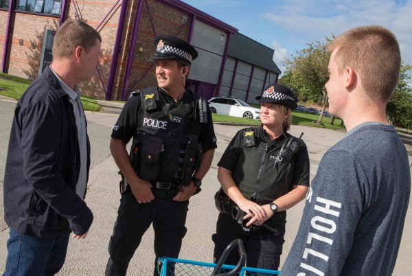 Two police officers speak to students on the streets