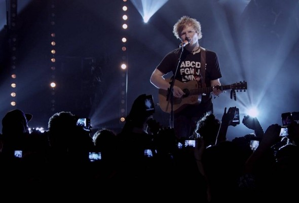 Singer-songwriter, Ed Sheeran, playing acoustic guitar live