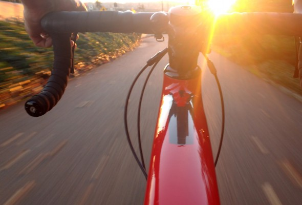 A close up shot of a red road bike from a point of view perspective