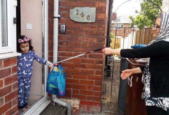 A woman hands a plastic bag of jigsaws and crafts - using a litter picker - to a child stood in a doorway, wearing plastic gloves