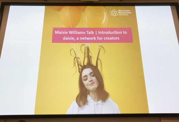 Maisie Williams, introducing Daisie background at front of lecture theatre