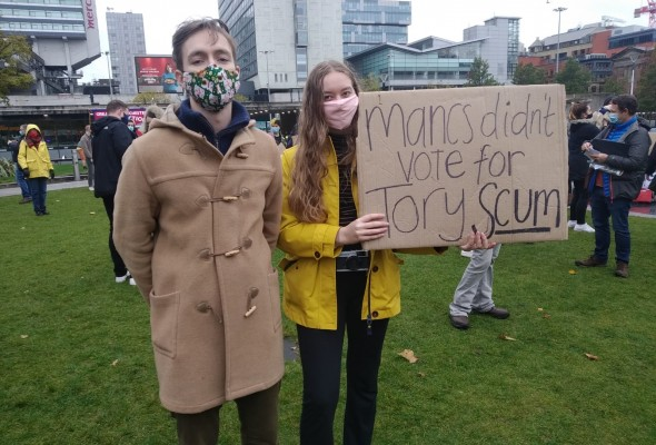couple, sign, protesting, masks, Manchester