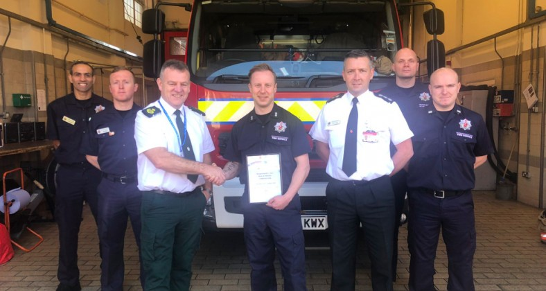 Karl Grindrod receives his award at Withington fire station