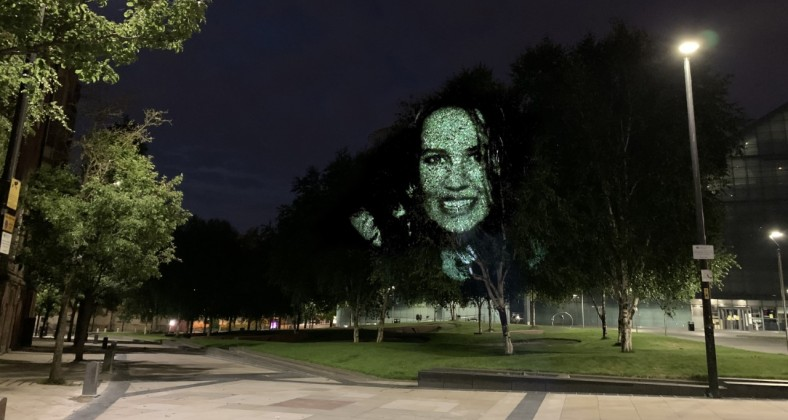 Charlene Karen Howie, a mum and carer. Her image projected on to a Himalayan Birch near the Football Museum in Manchester.
