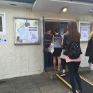 Image of two young women standing in line at a polling station.