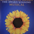 Calendar Girls the Musical promo art showing the title and a large sunflower on a blue background