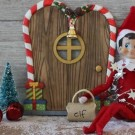 Elf on The Shelf doll sitting in front of a gingerbread house style door
