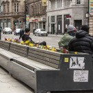 Members of public sat on a bench in city centre.