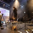 Image of several people during the soundcheck of singer Caoilfhionn Rose. Three people stood on raised platforms behind cameras filming.