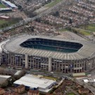 view of large stadium from sky with surrounding houses and fields