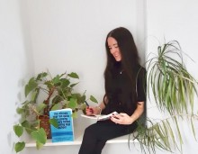 A young women with long dark hair sits reading a book, surrounding by books and plants