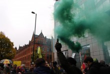 Protestor setting off green flare at United Against Fracking protest