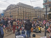Thousands of protestors sit on the tram line
